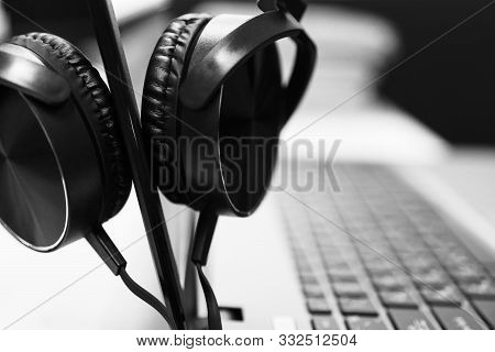 Black Headset Or Headphone On Laptop Keyboard For Helpline Customer On Communication And Hotline Sup