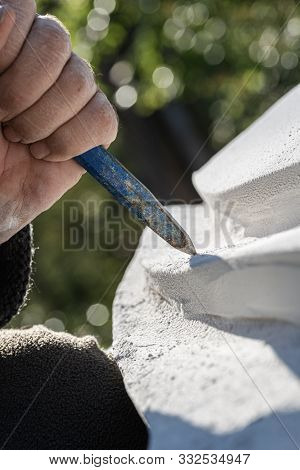 Closeup Of An Artist Working In White Stone Carving Curves With A Chisel.
