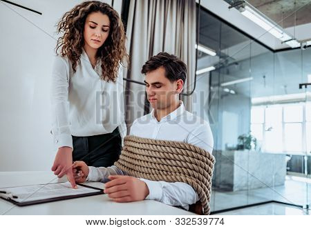 Business Concept The Employee Does Not Want But Must Sign The Document Against His Will. A Man Tied