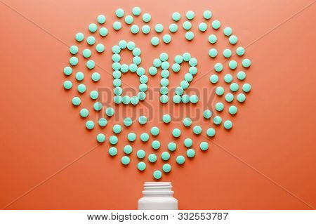 Vitamins B 12 In The Shape Of A Heart On A Red Substrate, Poured Out Of A White Jar.