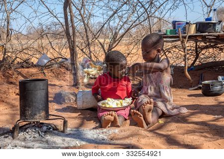 two african children in a village near Kalahari desert, the sister feeding her brother in the outdoors kitchen