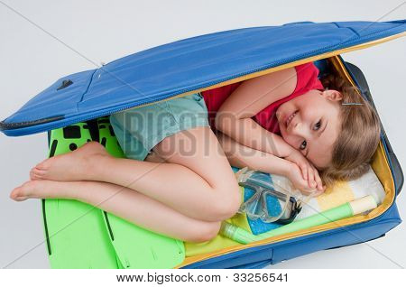 Travel, summer vacation - lovely girl inside suitcase ready for travel