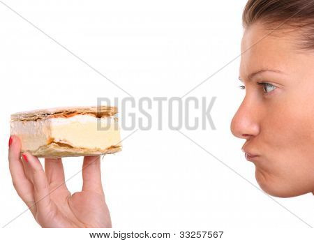 A close up of a young woman trying to resist temptation of eating a cream puff over white background