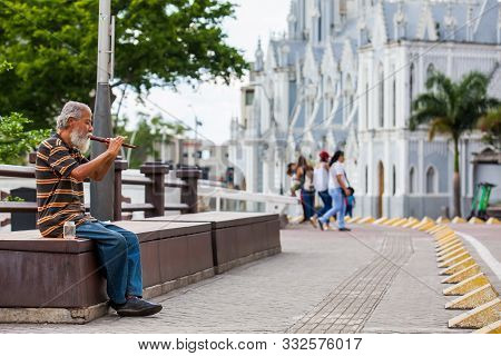 Cali, Colombia - October, 2019: Old Man Playing His Flute To Get Money At The River Boulevard In Cal