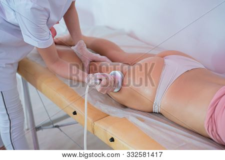 Woman in a beauty salon. Ultrasonic massage of the female buttocks and hips against cellulite and excess weight. Hardware figure correction. The doctor conducts the cavitation procedure for the girl. poster