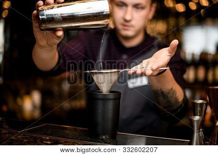 Male Bartender Pouring A Alcoholic Drink From The Steel Shaker To The Black Glass Through The Sieve