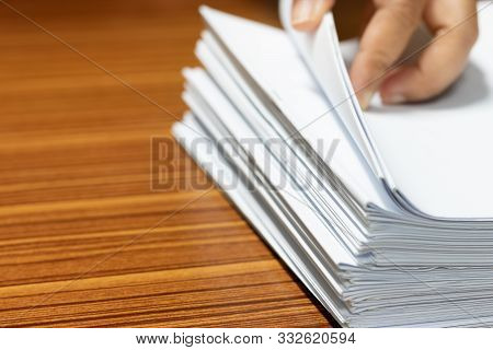 Teacher Searching Homework Assignment On Wood Desk In School Office For Score, Managed And Inspected
