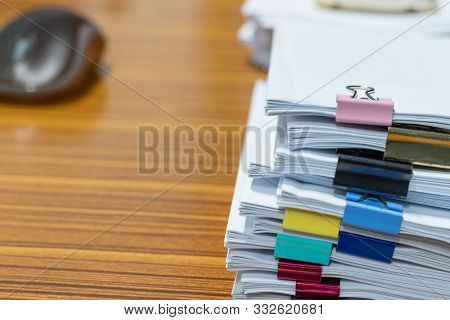 Pile Of Unfinished Paperwork Stacked In Archive With Paperclips On Desk In Office Waiting To Be Mana