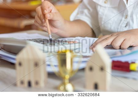 Blur Of Home And Businesswoman Use Calculator For Analyzing Data Of Market Report For Loan Home. Con