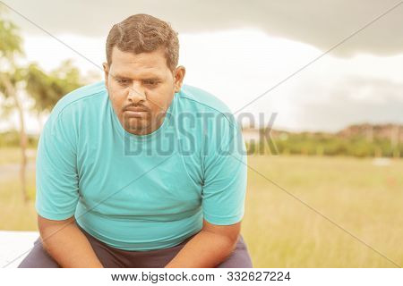 Seriously Fat Man On Outdoor, Park - Concept Of Sadness Due Overweight - Indian Obese Man Feeling Un