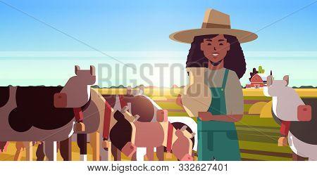 Milkwoman Holding Pail With Fresh Milk Female Farmer Standing Near Herd Of Cows Grazing On Grassy Fi