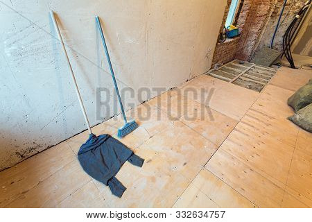 House Cleaning Equipment Such As A Mop With Rag In Apartment That Is Under Construction, Remodeling,