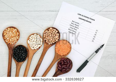 Low glycemic list with values for diabetics with corresponding legumes in olive wood spoons. High in vitamins, minerals, anthocyanins, antioxidant & smart carbs. Below 55 on the GI index. Flat lay.