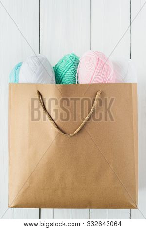 Oval Acrylic Colorful Wool Yarn Thread Skeins Lying In Kraft Paper Brown Bag On White Wooden Table B