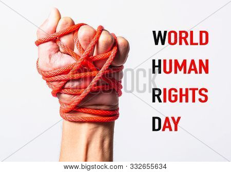 Red Rope On Fist Hand With World Human Rights Day Text On White Background, Human Rights Day Concept