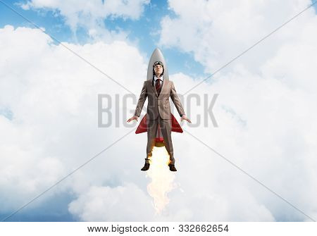 Businessman In Suit And Aviator Hat Flying On Rocket In Stratosphere. Superhero Businessman Flying W