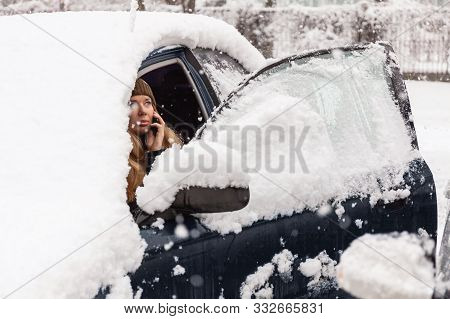 Young Woman Calling For Help Or Assistance Inside Snow Covered Car.  Engine Start In Frost. Breakdow