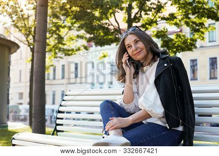 Cheerful Beautiful European Female In Her Fifty Enjoying The Nice Summer Weather Outdoors, Sitting O