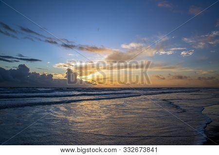 A Cloudy Sunrise At The Sandy Beach..
