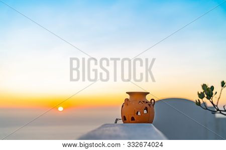 View beyond terra cotta urn and Greek Island architectural features to a Santorini sunrise as travel or background image. poster