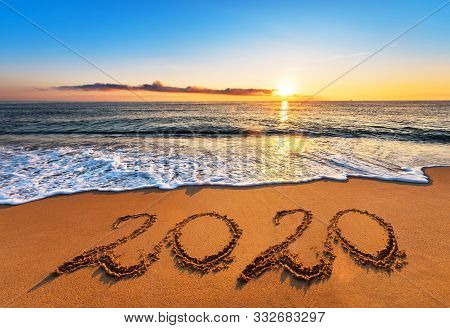 Number 2020 Written On Seashore Sand At Sunrise. Happy New Year 2019 Concept.