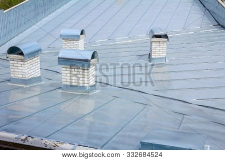 Chimney Made Of White Bricks For Ventilation On The New Galvanized Metal Roof.