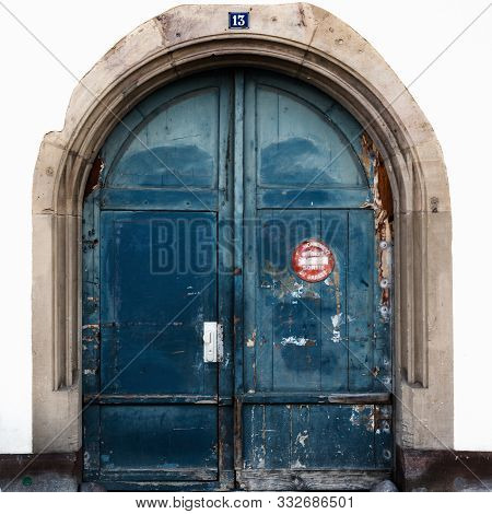 Detail View Of A Large Blue Arched Wooden Doorway With A Sign In French Saying
