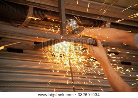 The Worker Is Sawing And Cutting Metal Part Of Billboards Steel In A Shop.
