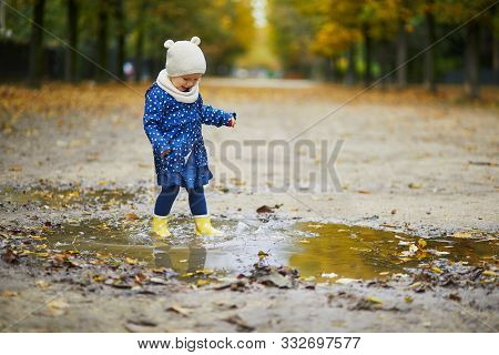 Child Wearing Yellow Rain Boots And Jumping In Puddle On A Fall Day. Adorable Toddler Girl Having Fu