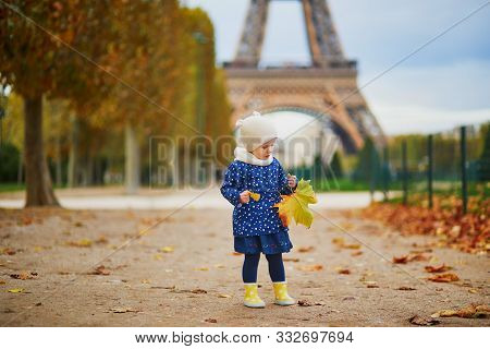 Adorable Toddler Girl In Blue Raincoat Toddler Girl Gathering Yellow Fallen Leaves Near The Eiffel T