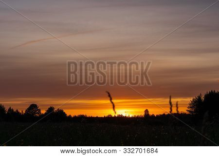 Sunset Over The Summer Meadow. Beautiful Scenic Sunset With Rays Of Sun Shining Through Clouds In Sk