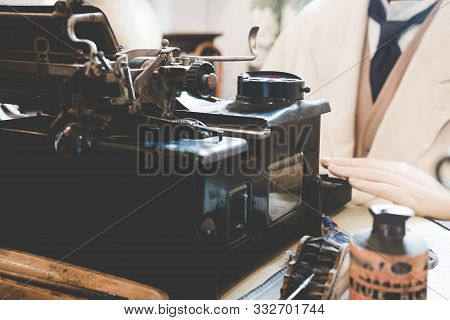 Vintage Antique Typewriter With Pipe On The Old Table And Hand Of Old Man Typing Letter On Vintage O