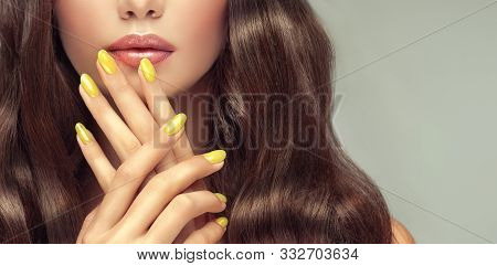 Beautiful Girl Long , Curly Hair . Model Woman Showing A Yellow Manicure On Nails . Cosmetics And Ma