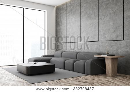 Corner Of Minimalistic Living Room With Concrete And White Walls, Wooden Floor, Comfortable Gray Sof