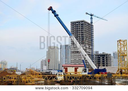 Installation Of A Tower Crane. A Truck Crane Lifts A Load At A Construction Site.installation Of A T