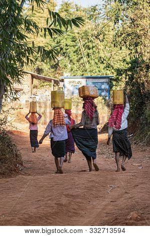 Kalaw, Myanmar - January 31, 2018: Burmese Women In Traditional Outfits Carrying Water On Their Head