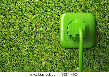 Green power cord in wall socket on grass background with copy space - eco or green power consumption concept, 3D illustration poster