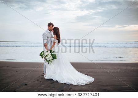 Elegant Gorgeous Bride And Groom Walking On Ocean Beach During Sunset Time. Romantic Walk Newlyweds