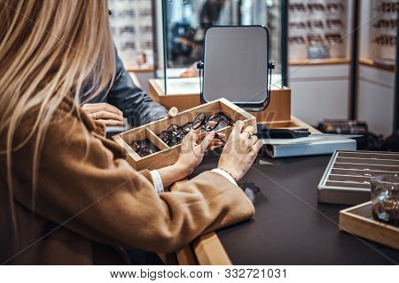 Professional Salesperson Helps A Woman To Choose Reading Glasses In An Optometric Shop.