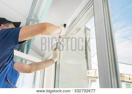 Worker With A Rubber Mallet Inserts A Glass Into The Frame Of A Plastic Window