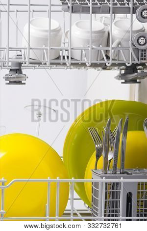 Green And Yellow Plates Are In The Basket Of The Dishwasher, Close-up