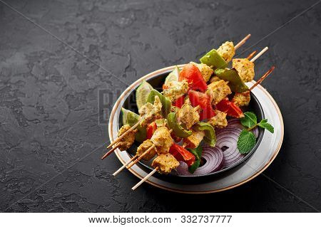 Chicken Tikka At Skewers In Black Bowl At Dark Slate Background. Chicken Tikka Is An Indian Cuisine