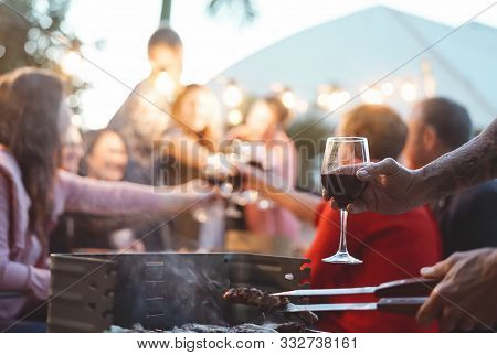 Happy Family Doing Celebratory Toast At Barbecue Party - Young And Older Parents Having Fun Dining T