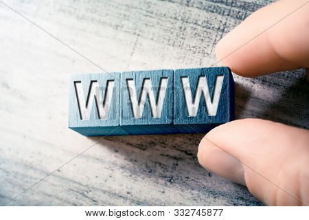The Word Www On Wooden Blocks And Arranged By Male Fingers On A Table