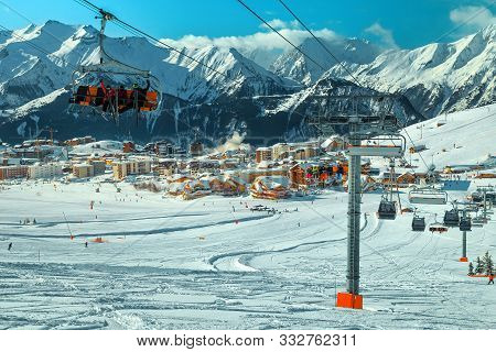 Stunning Alpine Winter Ski Resort In French Alps. Amazing Cityscape With Ski Lifts, Cable Cars And F