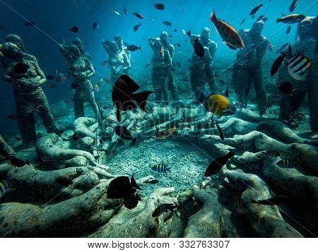 Beautiful Underwater View Of Bask Nest Sculpture Surrounded By Colorful Fish At Bottom Of The Sea In