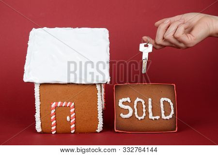 The Hand-made Eatable Gingerbread House, Hand With Key On Red Background