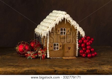Gingerbread house on rustic wood against a dark background