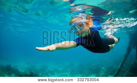 Happy Little Kid In Snorkeling Mask And Wetsuit Jump And Dive Underwater In Coral Reef Sea Lagoon. F