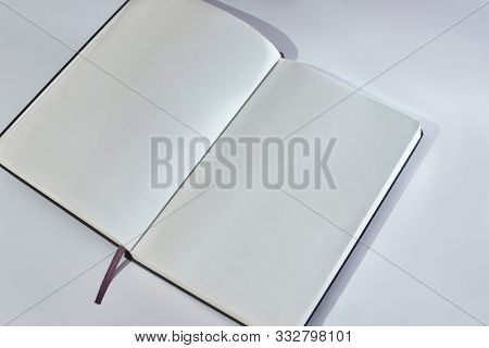 Empty noteblook blank bages on a smooth white desk